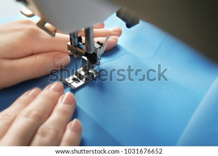 Woman sewing on machine with blue thread, closeup #1031676652