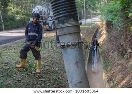 """Muadzam Shah, Malaysia - February  21st, 2018 :  Municipal worker """"Alam Flora"""" uses water spray jets and suction machines to clean rubbish and sand in the drain and put into a garbage truck. #1031683864"""