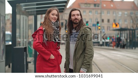 Smiling couple looking away while waiting at tram stop in a city. #1031699041