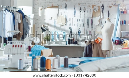 Shot of a Sunny Fashion Design Studio. We See Working Personal Computer, Hanging Clothes, Sewing Machine and Various Sewing Related Items on the Table, Mannequins Standing, Colorful Fabrics. #1031742880