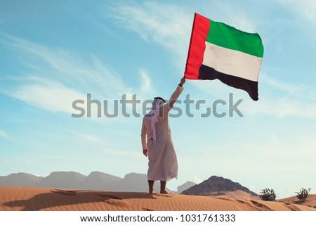 Proud arabian Emirati man holding a UAE flag in the desert  #1031761333