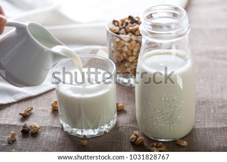 Nut milk pouring from the pitcher into the glass with bottle of milk and nuts #1031828767