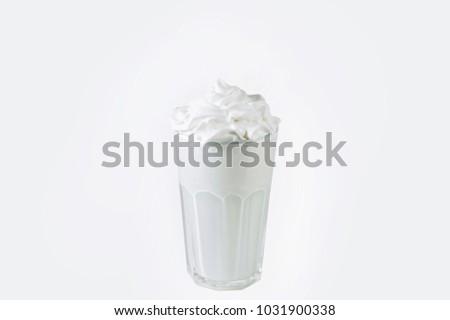 Glass of milk cocktail with white cream isolated on white. Fresh vanilla milkshake. #1031900338