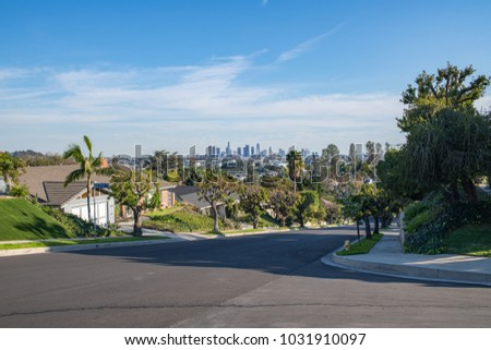 Los Angeles, CA: February 16, 2018:  A Los Angeles residential street with the Downtown Los Angeles skyline in the background.  Los Angeles is the second largest city in the United States. #1031910097
