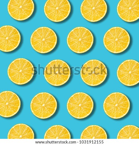 Lemon slices pattern on vibrant turquoise color background. Minimal flat lay food texture