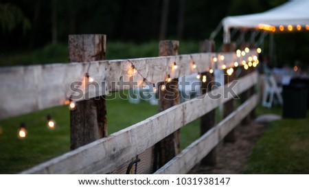 String of Lights on a Wooden Fence at Dusk #1031938147