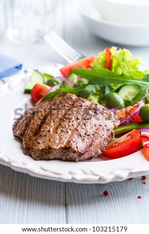 Juicy grilled beef steak with tomatoes, green pepper, organic green olives, cucumber, lettuce and fresh rocket. Concept for healthy nutrition. Tasty and healthy meal. Bright wooden background.  #103215179