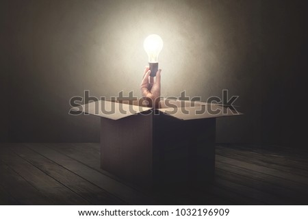 hand holding light bulb coming out from a paper box