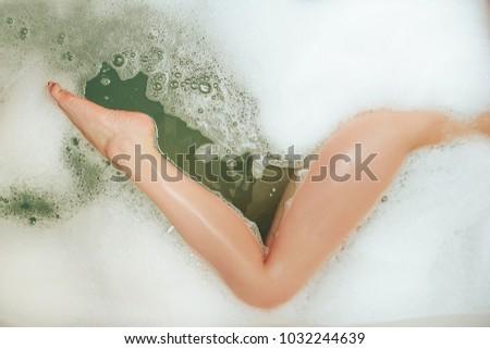 Beautiful girl foot taking foam bath #1032244639