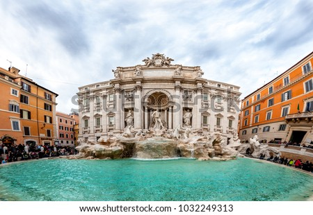 Rome, Italy - Dec 25, 2017 - Fountain di Trevi, surrounded by crowd of people willing to take a photo and dramatic sky on the background #1032249313