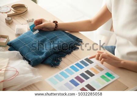 Female fashion designer holding color samples choosing fabric textile blue shades at workplace, dressmaker or tailor working at desk pointing at set palette making choice selection, close up view Royalty-Free Stock Photo #1032285058