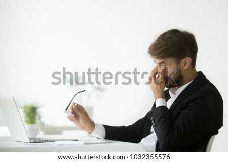 Eyes fatigue at work, tired exhausted businessman suffering from computer vision syndrome taking off glasses massaging eyes after long laptop use, overworked man feeling eye strain tension problem #1032355576