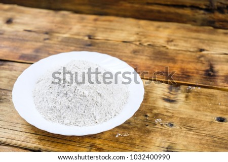Close-up heap with wheat flour coarse in white plate on wooden background. Left on the photo #1032400990