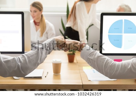 Colleagues giving fist bump, two male coworkers greeting, teammates celebrating corporate teamwork good result success concept, support in collaboration, friendship at work, close up view of hands Royalty-Free Stock Photo #1032426319