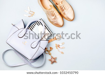 Cute blue ladies bag, stylish golden shoes and  feminine accessories . Flat lay, top view. Spring fashion concept in pastel colored  Royalty-Free Stock Photo #1032450790