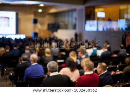 Speaker on the podium. People at conference hall, rear view. Speaker at Business Conference and Presentation. Audience at the conference hall. Abstract blurred photo of conference hall. #1032458362