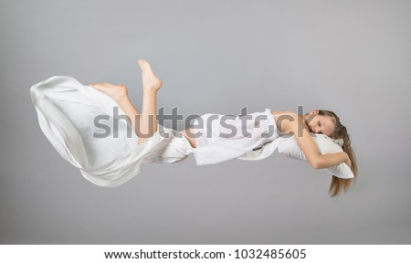 Sleeping girl. Flying in a dream. White linen flying through the air. Light grey background #1032485605