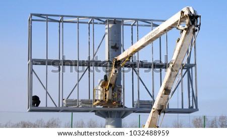 Construction site and big billboard. People Working Building New Big Billboard. Worker repairing billboard. Construction of LCD screen billboard #1032488959