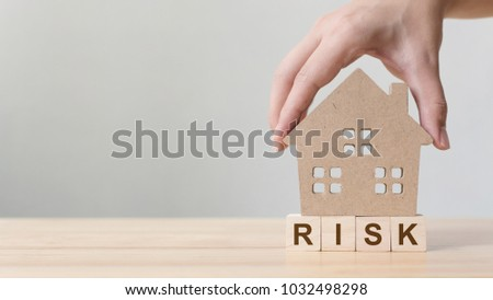 """Property investment and house mortgage financial. Risk management concept. Hand putting wooden home on wood block with word """"risk"""" #1032498298"""