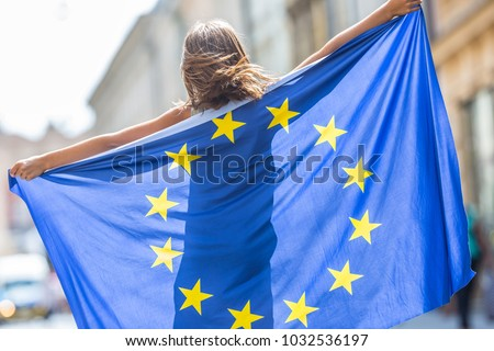 Cute happy young girl with the flag of the European Union. Royalty-Free Stock Photo #1032536197