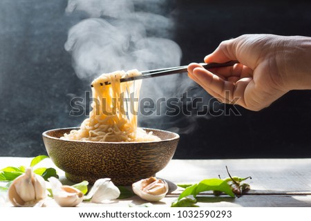 Hand uses chopsticks to pickup tasty noodles with steam and smoke in bowl on wooden background, selective focus. Asian meal on a table, junk food concept #1032590293