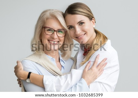 Happy beautiful older mother and adult daughter embracing looking at camera, smiling senior lady hugging young woman, family of different age generations bonding hugging, head shot portrait Royalty-Free Stock Photo #1032685399