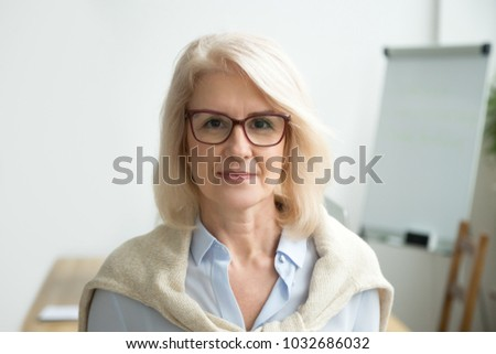 Confident aged businesswoman wearing glasses looking at camera, skilled experienced senior female professional, mature lady teacher coach posing in office alone, older woman boss head shot portrait #1032686032