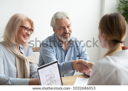 Smiling satisfied senior couple making sale purchase deal concluding contract handshaking real estate agent or realtor, happy older family and broker shake hands agreeing to buy new house at meeting #1032686053