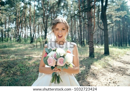 Beautiful bride in fashion wedding dress on natural background.The stunning young bride is incredibly happy. Wedding day. .A beautiful bride portrait in the forest. Royalty-Free Stock Photo #1032723424