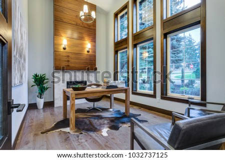 Spacious Masculine home office design with walnut veneer fireplace and oversized windows.