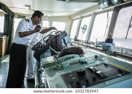 CHONBURI, THAILAND, FEBRUARY 2017: Unidentified Cargo Ship sailing on sea and People working on ship as safety #1032782947