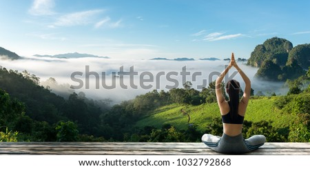 Young woman practicing yoga in the nature.female happiness. Landscape background Royalty-Free Stock Photo #1032792868