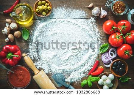 Ingredients and spices for making homemade pizza. Top view with copy space on wooden table  Royalty-Free Stock Photo #1032806668