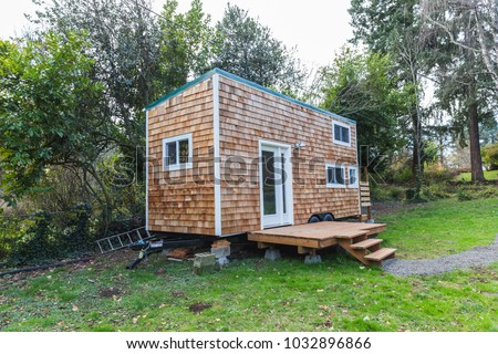 Portable tiny home with wood siding in the back yard of a larger property. Forest Grove, Oregon, USA. #1032896866