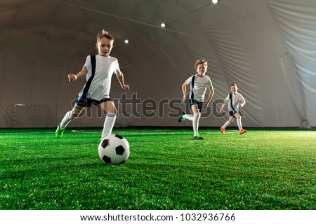 Three boys in uniform running after ball down green field while training indoors #1032936766
