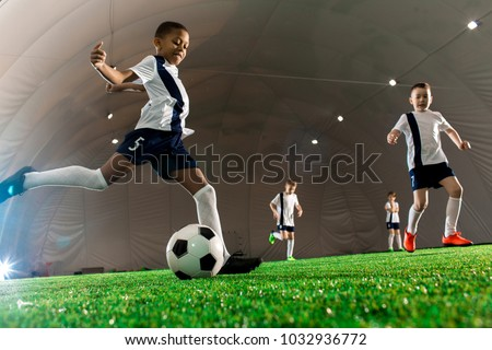 Team of intercultural boys running throughout football field, one of them kicking the ball #1032936772