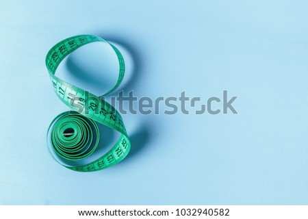Measuring tape in the form of eight on a blue background Royalty-Free Stock Photo #1032940582