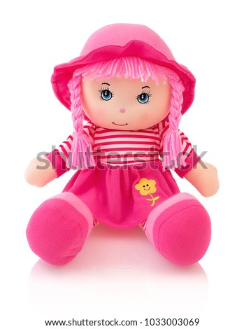 Pink plushie doll isolated on white background with shadow reflection. Cute pinky rag baby doll sitting on white underlay. Nice contemporary rag baby with pink hair. Modern joyfully rag baby with cap. #1033003069