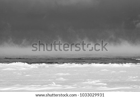 Sea smoke in winter. The Baltic Sea on a cold February morning in Latvia. Steam fog. Black and white, graphic horizontal  #1033029931