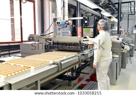 Production of pralines in a factory for the food industry - conveyor belt worker with chocolate