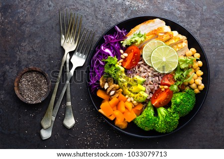 Buddha bowl dish with chicken fillet, brown rice, avocado, pepper, tomato, broccoli, red cabbage, chickpea, fresh lettuce salad, pine nuts and walnuts. Healthy balanced eating. Top view #1033079713