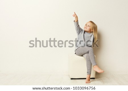 Portrait of a happy little girl sitting and pointing up with finger on white studio background, front view, copy space #1033096756
