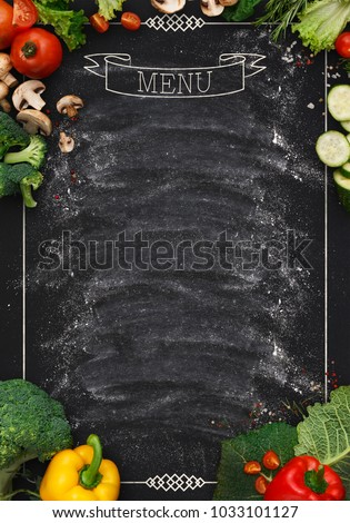 Design concept for restaurant menu mockup. Black rustic chalkboard with white inscription and vegetables frame, top view, copy space for text and logo, vegetarian cafe concept #1033101127