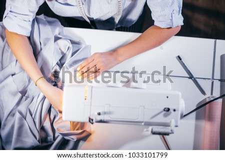 top view cropped photo of white working sewing machine with tailor's arms. clothers business #1033101799