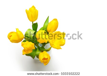 Bouquet of yellow tulips in a glass vase on a white. Top view. #1033102222