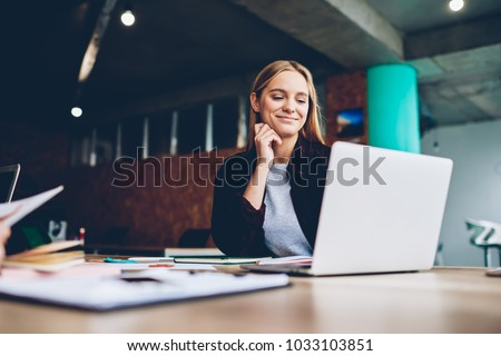 Successful female grapic designer watching tutorial about creative ideas at laptop computer during working process in office.Positive student with blonde hair reading business news on netbook Royalty-Free Stock Photo #1033103851