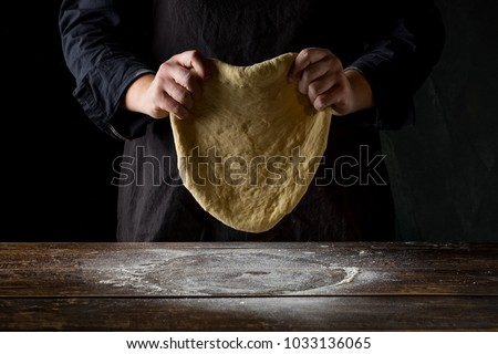 Chef hands preparing dough for italian pizza, pasta or bread preparation over wooden background, top view, flat lay #1033136065