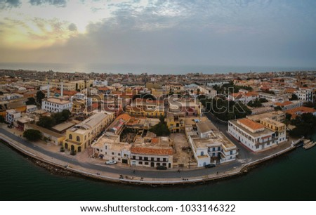 Aerial panorama of Sant Louis, a unesco heritage city in northern Senegal. View from Senegal river towards the old colonial city and fisherman island. #1033146322