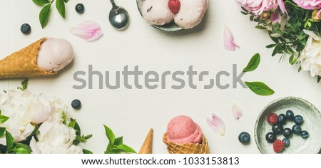 Flat-lay of pink strawberry and coconut ice cream scoops, sweet cones and peony flowers bouquet over white background, top view, copy space, wide composition. Summer food concept #1033153813