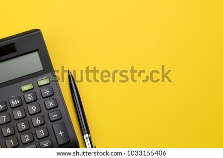 Flat lay or top view of black pen with calculator on vivid yellow background table with blank copy space, math, cost, tax or investment calculation. #1033155406